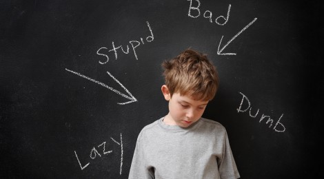 picture of bullied boy standing in front of hurtful words on chalkboard